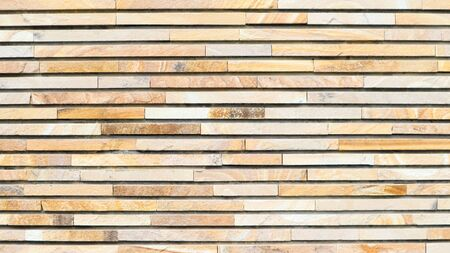 Decorative texture of a beautiful wall with rectangular parts made of multi-colored artificial stone. Collage of narrow granite blocks. Exterior finish with stone. Background from natural material