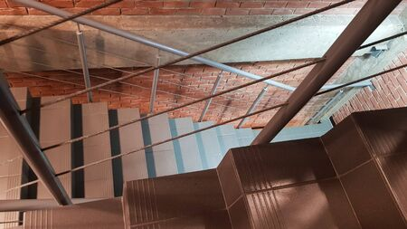 Red brick building with a modern staircase in a loft style with metal railing. Stairs adorn the building. Modern stairwell. Steel railing. Staircase in perspective