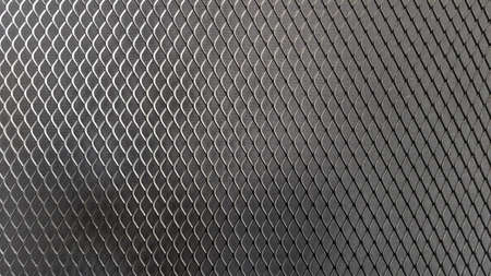 Metal mesh seamless pattern. Black metal mesh texture on a black background. Bulletin board for text and message design. Rhombus shape.