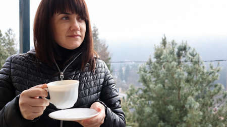 Beautiful happy woman with a white cup of coffee or tea enjoying the beautiful view of the mountain landscape in the morning fog from the balcony of her hotel room. Autumn and winter travel concept.
