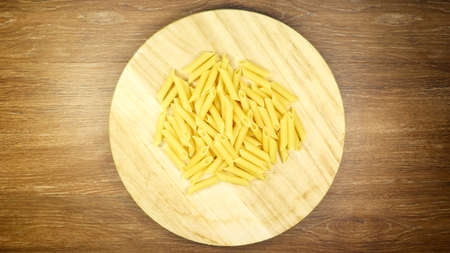 Penne Rigate Raw Pasta is a short pasta with oblique cuts and a ribbed surface. Traditional Italian pasta. Pasta background. Top view of Italian food ingredient on brown table 版權商用圖片