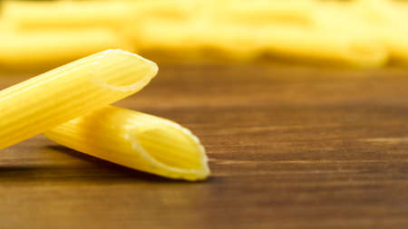 Penne Rigate Raw Pasta is a short pasta with oblique cuts and a ribbed surface. Traditional Italian pasta. Pasta background. Side view of Italian food ingredient on brown table. Copy space. 版權商用圖片