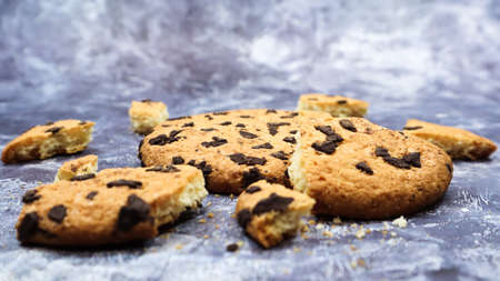 One soft freshly baked chocolate chip cookie with crumbs and chunks on a gray marble kitchen countertop. American traditional pastry, dessert. Delicious sweet food