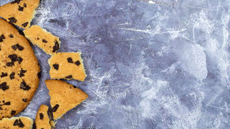 One soft freshly baked chocolate chip cookie with crumbs and chunks on a gray marble kitchen countertop. American traditional pastry, dessert. Delicious sweet food. Flat lay. Copy space.