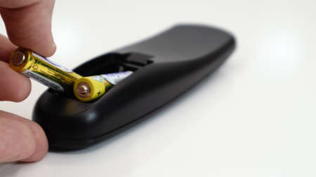 Insert the AAA size battery into the remote control. Installing batteries in the wireless device. A male hand holds a yellow alkaline battery. Text in English and Russian