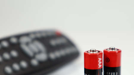 Black TV remote control with AAA alkaline batteries in red and white on a white background. Battery replacement, spare parts. Remote control battery compartment close-up 免版税图像