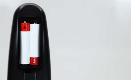 Black TV remote control with AAA alkaline batteries in red and white on a white background. Battery replacement, spare parts. Remote control battery compartment close-up. Copy space. 免版税图像