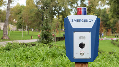 Emergency button in a public city park with an English word emergency. SOS, police, panic. People safety concept. Emergency call for help