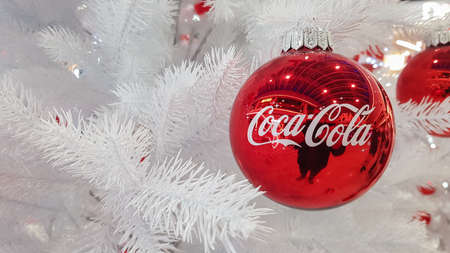 Coca Cola Christmas red ball decoration. Marketing from the world leader in carbonated drinks. Coca Cola advertisement Christmas tree decoration. Ukraine, Kiev - January 05, 2021.