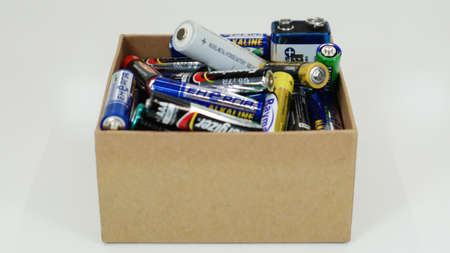 A cardboard box on a white background full of used household AA, AAA, PP3 alkaline batteries collected for recycling. Recycling and ecology problems. Ukraine, Kiev - January 7, 2021.
