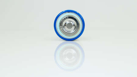 Large battery type D or C cell on white background with reflection. View of a metallic alkaline battery with copy space. Mandatory processing
