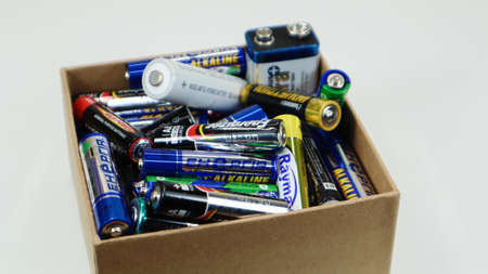 A cardboard box on a white background full of used household AA, AAA, PP3 alkaline batteries collected for recycling. Recycling and ecology problems. Ukraine, Kiev - January 7, 2021
