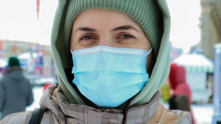 Portrait of happy young woman wearing medical protective mask outdoors and looking at camera. Virus protection. A woman outdoors on a winter day stands in a hat and a hood in the park Foto de archivo