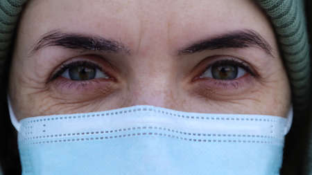 A beautiful young woman with a medical mask on her face is looking at you in the camera. Close-up portrait, fear in the eyes. Perfect eyes. Winter. Coronavirus protection. Health and safety concept
