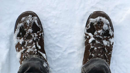 Male legs in snow-covered winter boots, top view. Winter walk in the snow. Focus on your legs. Beautiful white winter weather with fresh snowfall