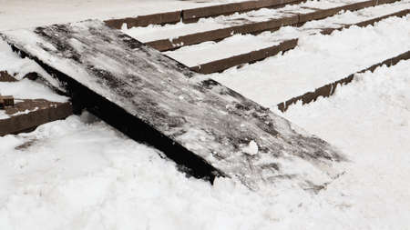 Snow covered slippery concrete stairs and wooden ramp. First snow on granite stone steps Foto de archivo