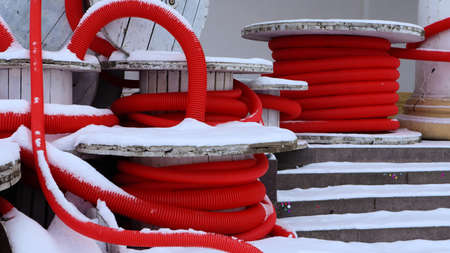 Large coils of red flexible corrugated pipe used to protect cables in electrical installations. Lots of colored polyethylene plastic hose used in construction for plumbing systems