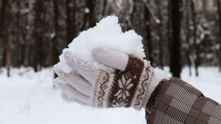 Women's hands in knitted mittens hold natural soft white snow outside on a winter day. Joyful winter time. Hand holds cold snow. Spending time in nature in winter Foto de archivo