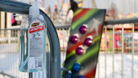 Disinfectant near the ticket booth in an amusement park. Close-up of a disinfectant with a label that has English text for visitors to the amusement park. Ukraine, Kiev - January 14, 2021 Editorial