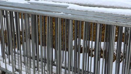 A portable metal event fence is kept in one place at the fair in the snow outdoors in winter. Gray grates for cluttering the area and organizing the queue for the event Foto de archivo