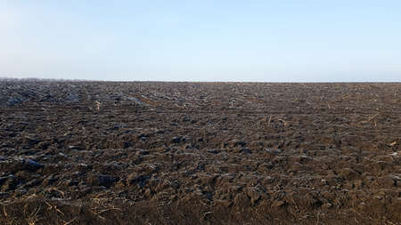 Agricultural field plowed by tractors under blue sky. The field has been plowed, crops have been sown. Close up of soil texture. Rural scene. Farming and food industry. Arable land of chernozem. Foto de archivo