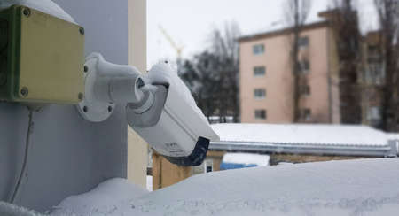 Large white surveillance camera over a window against the backdrop of a public building. close-up. CCTV camera installed on the outer window of the house.