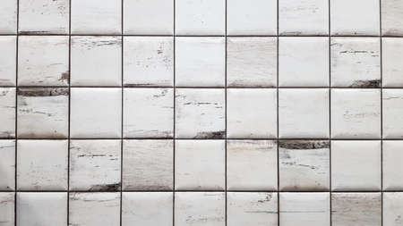 White aged tiles background. Seamless texture tiles. Old white small square dirty tiles on the wall Foto de archivo