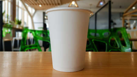 Paper white coffee cup disposable to take or go, on the wooden table of the coffee shop or dining room, place for a designer layout. Hot coffee cup in a cafe. Foto de archivo