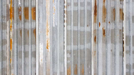 A rusty and weathered piece of corrugated metal. Corroded galvanized iron sheet. old zinc wall background