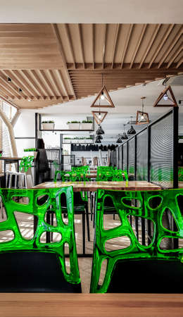 Cafeteria, no people dining room with wooden tables and green chairs. Interior with wood and metal elements. Modern dining areas with window lighting. Ukraine, Kiev - February 19, 2021. Editorial