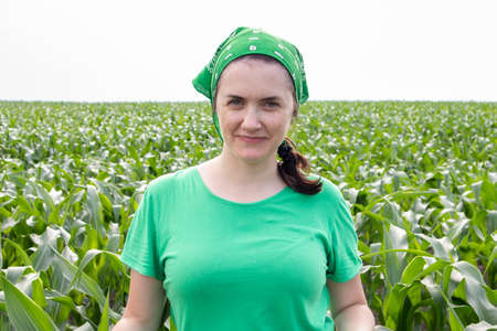 Beautiful smiling young woman farmer in green t-shirt and green sun hat standing in the middle of a green corn field on a sunny summer day outdoors. Harvest time. Organic farming. Sunlight