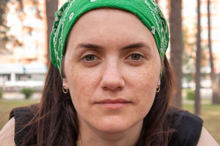 Close-up portrait. Beautiful young woman without makeup in a black T-shirt and a green headdress from the sun on a sunny summer day outdoors. Sunlight