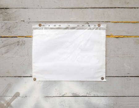 White paper sign with rivets, vintage background on a gray wooden old backdrop. Wooden textured wall, weighs a white blank cardboard sign lit by the sun, closeup. Stockfoto