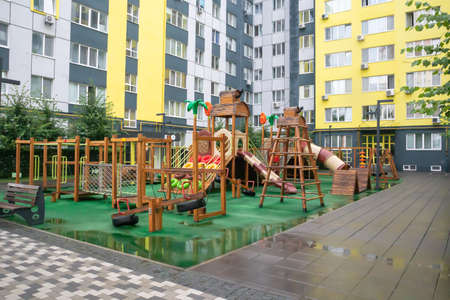 A courtyard of high-rise buildings with a modern and large playground made of wood and plastic on a rainy summer day without people. Empty outdoor playground. A place for children's games and sports