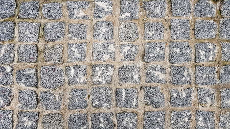 surface paved with black road tiles. top view. Granite paving stones on a sidewalk or pavement textured paving background. Close up top view