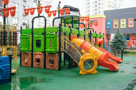 A courtyard of high-rise buildings with a new modern colorful and large playground on a rainy summer day without people. Empty outdoor playground. A place for children's games and sports Stockfoto