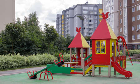 An empty modern playground in the courtyard of residential buildings without people and children. Security and protection measures against COVID-19 in the city park. The concept of childhood is over Stockfoto