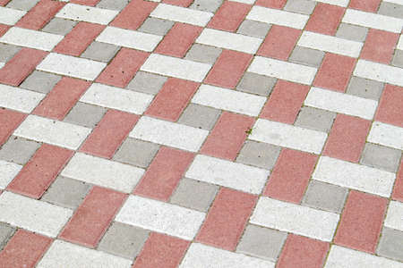 Concrete or paved newly laid gray and red paving slabs or stones for floors or walkways. Concrete paving slabs in the backyard or road paving. Garden brick path in the courtyard on a sandy foundation Stockfoto