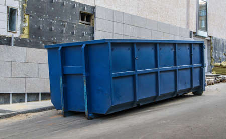Metal durable blue industrial trash bin for outdoor trash at construction site. Large waste basket for household or industrial waste. A pile of waste Stockfoto