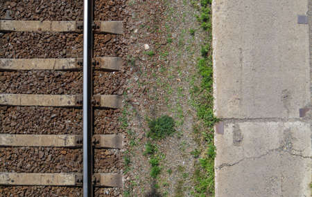 Railroad top view, flat lay. Part of the track for trains. Aerial view of a railway from a drone. Background with space for text. Shiny iron rails and concrete sleepers