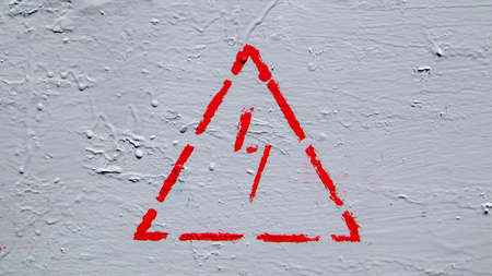 Red electrical hazard sign with lightning in a triangle on a gray painted metal junction box