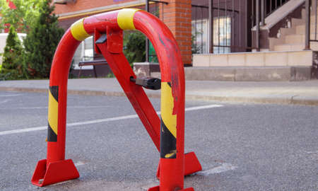Manual red metal parking barrier with lock. Parking lock device. Parking barrier installed. A foldable barrier prevents the vehicle from stopping at this point. Reserved seat