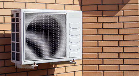 Close-up shot of a modern climate control unit against the background of a brick wall of the facade of a house outside. Air conditioner on the wall with space for text. Air compressor
