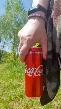 Hand holding a can of Coca Cola. The drinks are produced by the American beverage corporation The Coca-Cola Company. Young woman with Coca-Cola outdoors, close-up. Ukraine, Kiev - August 19, 2021