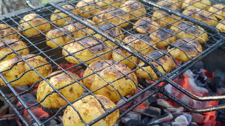 Grilled potatoes with bacon, whole baked on the barbecue grill. Selective focus. Whole small potatoes with bacon bits and grilled. Baked potatoes with grilled bacon Stockfoto