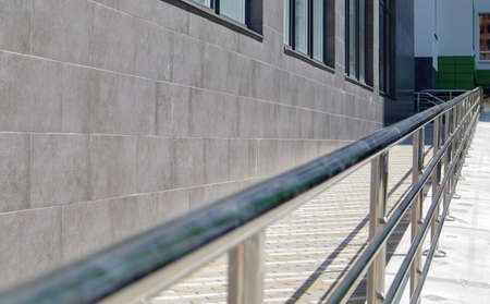 A ramp with stainless steel handrails for wheelchairs, bicycles and strollers with children in front of the building. Handrail for lifting a wheelchair. Shiny stainless steel handrail