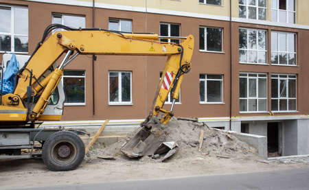 Mobile crane loader of yellow color on the background of a building under construction. German-Swiss international equipment manufacturer. The excavator is used for earthworks