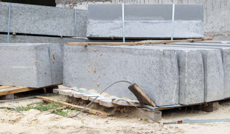 Faceted granite curbs on a pallet. Smooth porcelain stoneware products at the construction site. Curbstone, a stack of concrete curb boards prepared for installation. Road repair Stockfoto