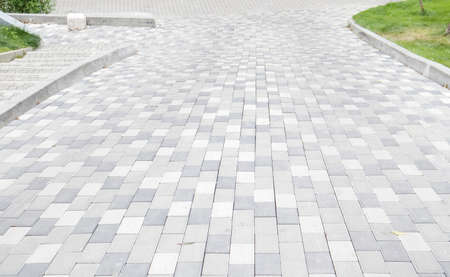 A long descent covered with gray paving slabs. The ramp is paved with concrete tiles. Wheelchair and bicycle accessibility concept Stockfoto