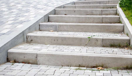 Steps from paving slabs and curbs. Rows of gray steps made of gray paving slabs are laid out evenly, consistently and tightly to each other. Paving stone steps slab gray background Stockfoto